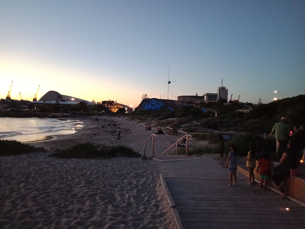 View of the Roundhouse and illuminated walls from the beach at twilight.