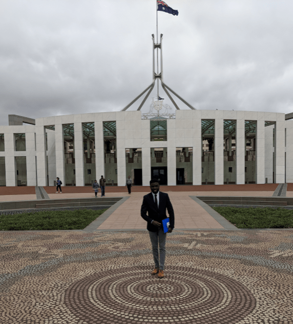 Fane Mensah standing in front of Parliament House Canberra